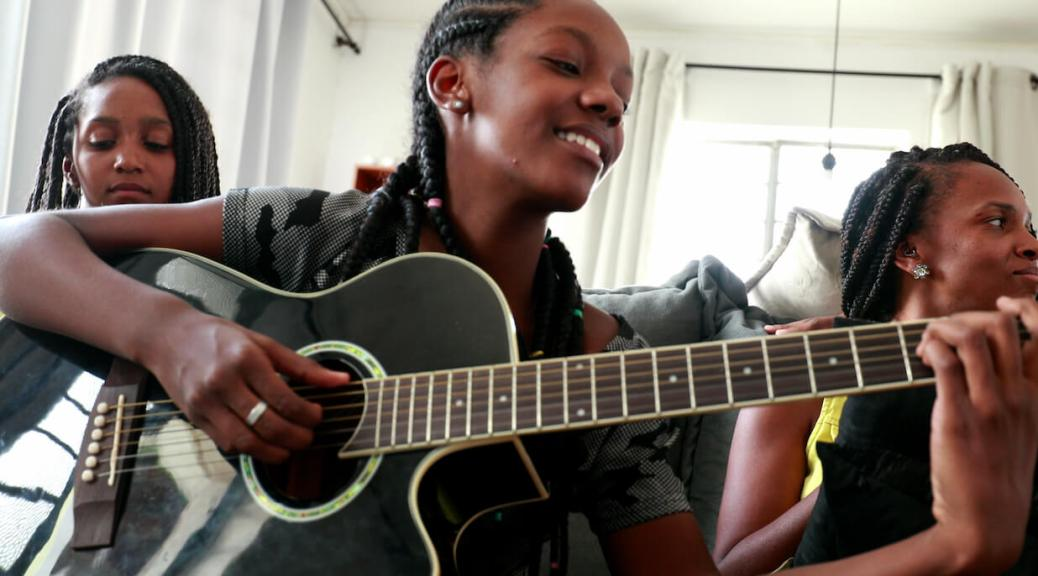 A smiling Black girl with braids plays guitar. another girl sits to the left of her and a woman to the right.