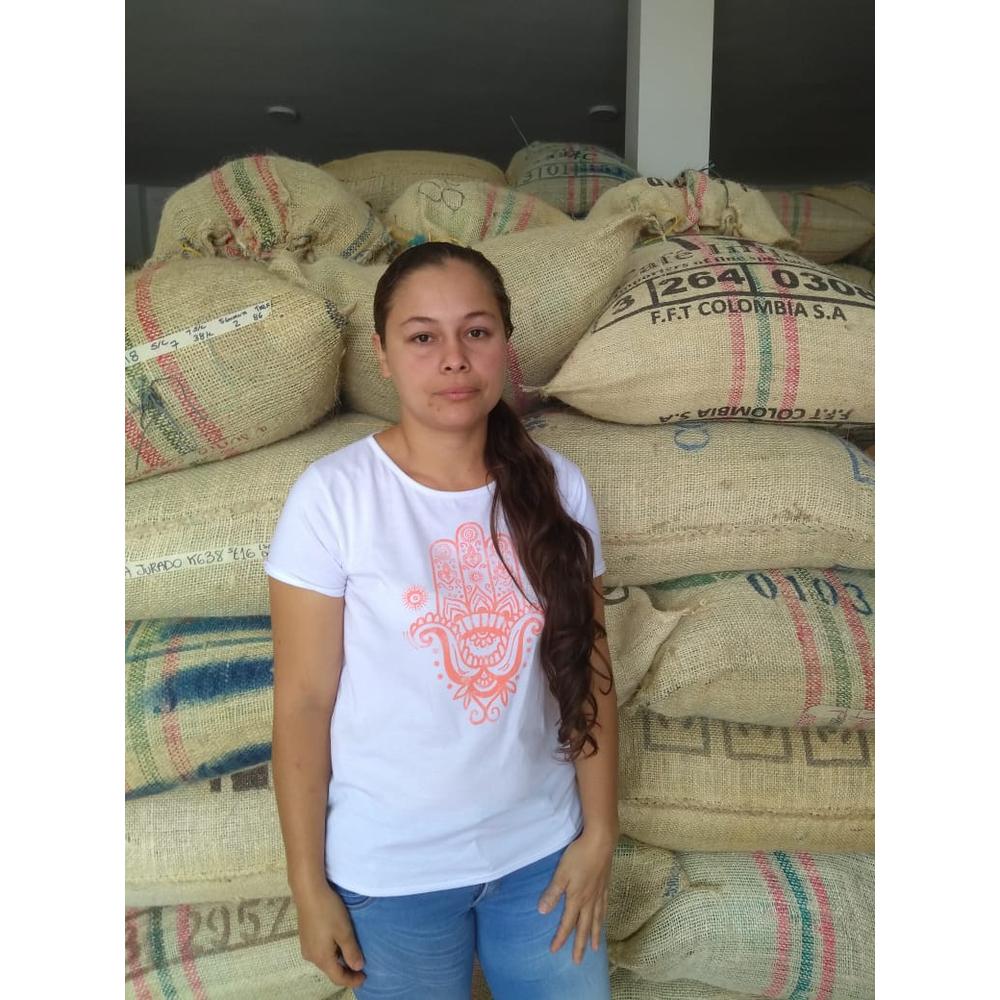 Photo of coffee farmer Sandra Jurado in front of Burlap bags from Acevedo Colombia
