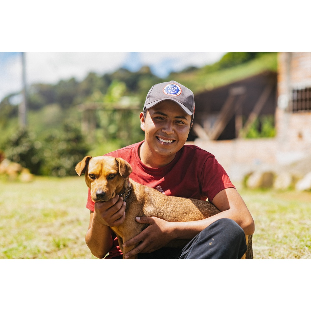 young coffee farmer holding his dog in a coffee farm in san agustin huila colombia