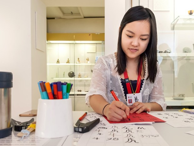 Woman writing on a piece of paper with a felt tipped pen. Museum display cases in the background.