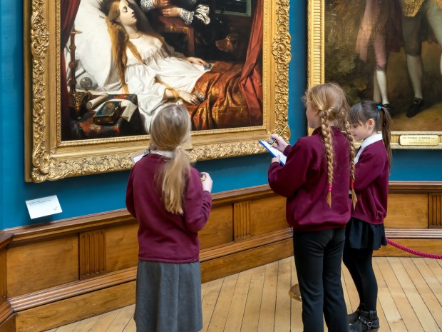 Group of school kids standing in front of a painting