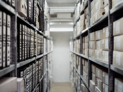 archival collection, looking down an aisle with archival boxes on shelves