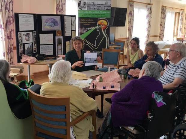 Residents of the care home sat around the table with museums objects and a curator presenting about the objects