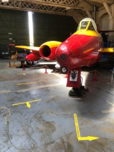 A red and yellow aeroplane on display in a hangar, with yellow directional arrows on the floor.