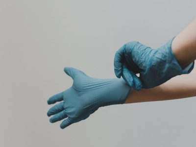 A pair of hands putting on some protective gloves