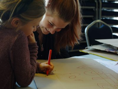 A volunteer helps a child with some drawing