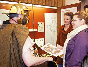 A man dressed as a historical figure speaks to visitors