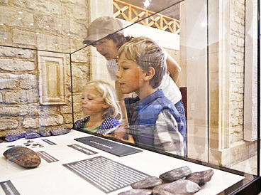 A family look into a museum case