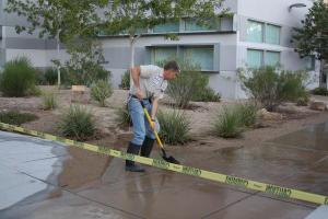 Engineer Mr. Steven Deberardinis pushes away the excess water to clear the area in front of the D building.<br />Photo Credit: Southwest Shadow Staff