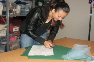Felicia Richardson, junior, is starting her prom dress by using a marking tool to outline her pattern piece for the challenge.<br />Photo Credit: Saron Abraham