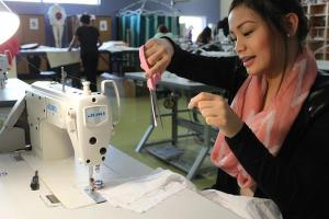 Andrea Salazar, junior, prepares to sew her muslin pants by cutting the extra threads off of the sewing machine.Photo Credit: Shantil Gamiao