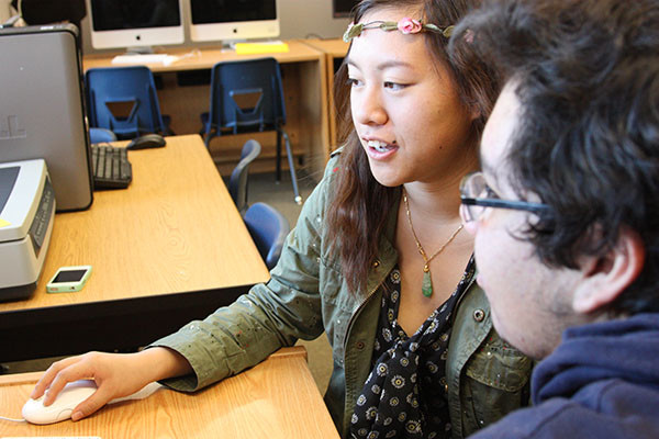 "Freshman Cynthia Sze Nga shows Kevin Camelo her portrait in the library. The project took a lot of time, and additional work outside of class helped. ""It's good to get feedback from others because they notice things you might have missed,"" Sze Nga said.  Photo credit: Amanda Galvan"