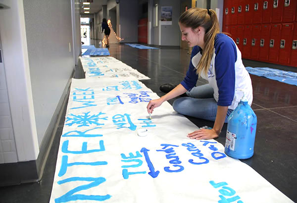 "Student Council member Adrianna Willeford paints a banner advertising ""Winter Week."" The week will take place from Oct. 15-19 and will consist of spirit dress up days and holiday themed lunch games. ""I'm really excited because I love the holiday season and I hope that the student body is ready to participate in some really awesome spirit days,"" Willeford said.   Photo Credit: Helen Abraha"