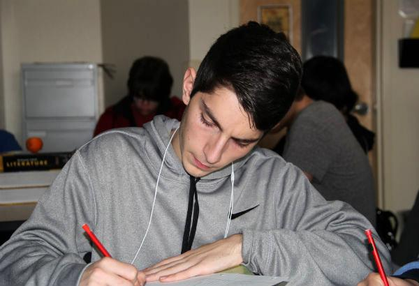 "Junior Stepan Gevorgyan participates in a timed essay in Advanced Placement (AP) Language and Composition. He had to write his essay in 30 minutes to practice for the AP exam. ""The timed writings we do in class for Mr. Davis strengthens me as a writer to better my understanding in literature and eventually create my own piece of work,"" Gevorgyan said.  Photo Credit: Migi Contreras"