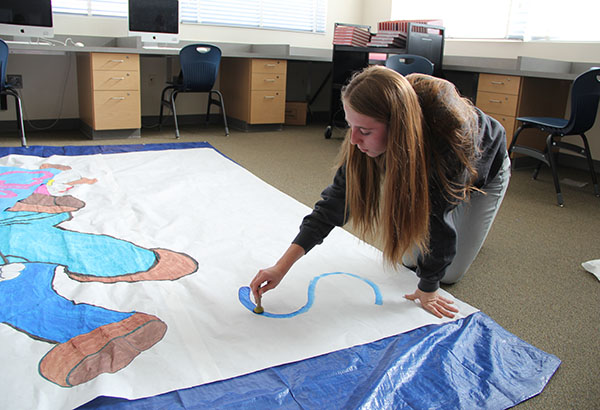 "Student Council member Zoey Kriethe creates a poster to ask someone to the Sadie Hawkin's dance on Feb. 17. The theme of the dance is ""GameOn!"" and Kriethe incorporated the theme by painting a photo of Mario. ""I think it's really good that we're doing a Sadie's dance and a game night because more people are likely to come,"" Kriethe said.  Photo Credit: Helen Abraha"