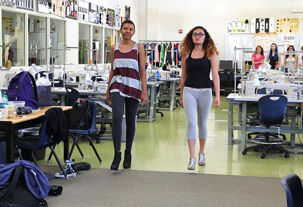 Seniors Christal Rhea and Victoria Bonanno walk the runway for the second time with a partner. Models were all required to walk down the runway three times to enhance and perfect their skills.Photo Credit: Mika Pagado
