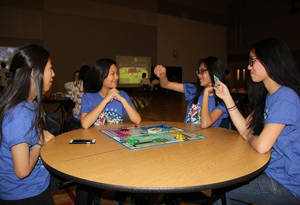 "Juniors Mary Allyn Maguddatu, Rachel Gomez, Angelica Mayor and Xueying Zheng engage in an exciting game of ""Sorry!"". The four attended the sixth annual Sadie Hawkin's dance on Feb. 28. ""I really enjoyed Sadie's with my friends because we would go dance and then play the games,"" Mayor said.  Photo Credit: Patricia Ascano"