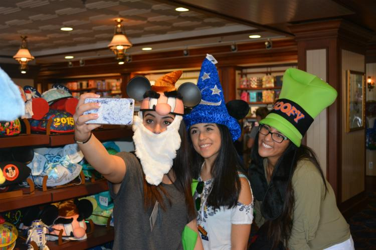 """Atena Sadri, Daniela Ornelas and Sathya Raghavan from Seven Lakes High School pose in silly hats. They decided to step into the cool shop and take a look at the souvenirs while exploring the boardwalk. """"We just wanted to escape the humidity for a bit and ended up taking selfies in weird hats to make us laugh,"""" Ornelas said."""