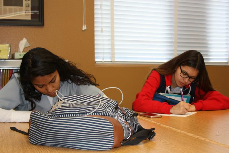 Writing as fast as they can to get the words written down are sophomores Monica Ortiz and Elisa Bustamante. This assignment consisted of writing a phone callers words down in a limited amount of time.