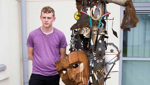 Alex Tucker standing with one of his sculptures