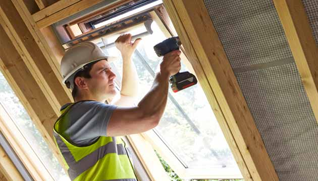 A builder installs a roof window