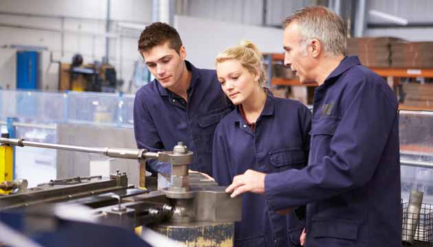 Two engineering apprentices working with their mentor
