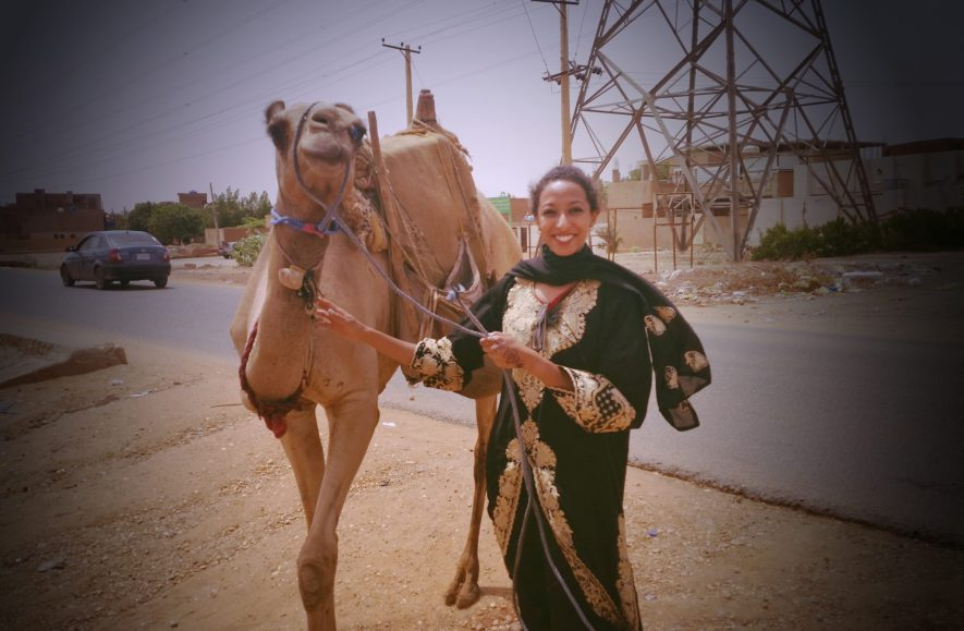 "Although more rare, camels also exist in Sudan and can sometimes be spotted in the streets. I found a man walking this one on my way to grandma's house. Here I'm wearing a traditional woman's dress in Sudan, an ""abaya""."