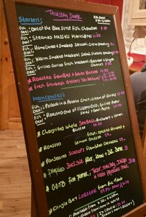 """The menu board at """"Out of the Blue,"""" a seafood restaurant in Dingle"""