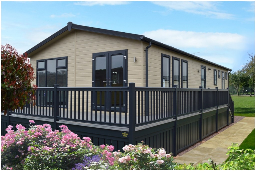 Resized - The summer haven holiday lodge - popular holiday lodge design - exterior photo with balcony, french doors and fencing