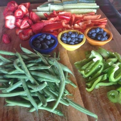 Wooden board full of fresh green beans, sliced green peppers, bowls of blueberries, sliced strawberries, strips of red pepper, and cucumber spears