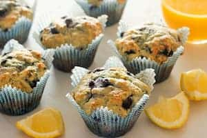 Lemon bluberry muffins spread out on a table with lemon slices