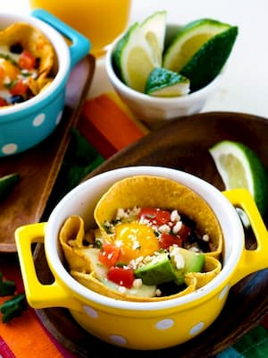 Bowl full of egg, veggies, and avocado with limes in the background