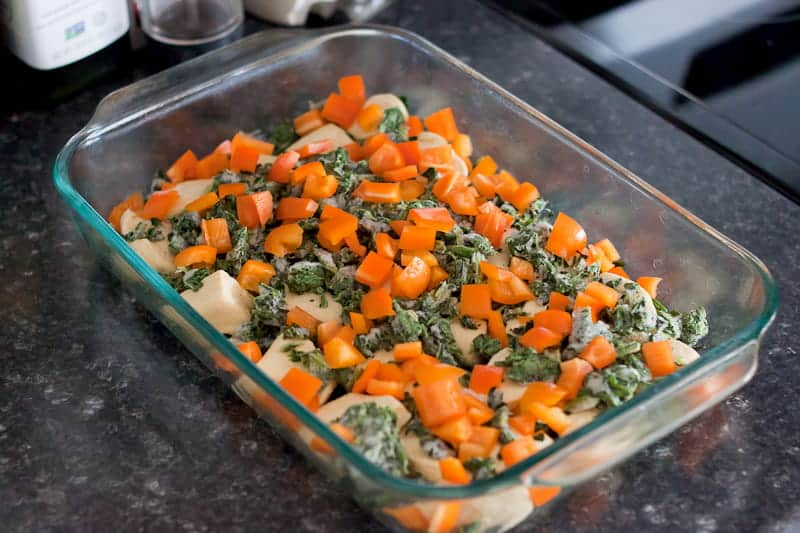 Baking pan with biscuits on the bottom and sprinkled with frozen spinach and diced bell pepper