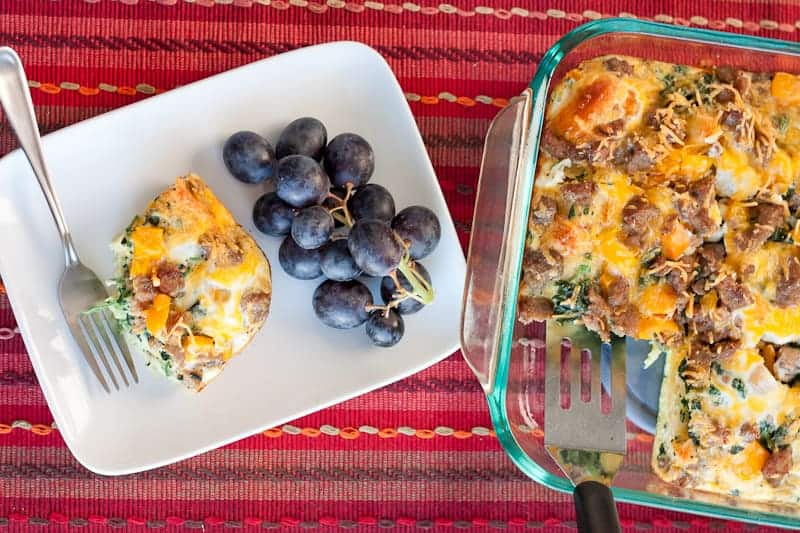 Overhead shot of healthy biscuit breakfast casserole in the baking dish and one slice on a plate with grapes next to it