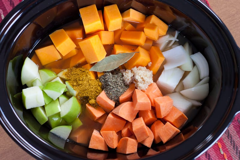 Slow cooker showing all of the soup ingredients - apple, sweet potato, onion, butternut squash, etc