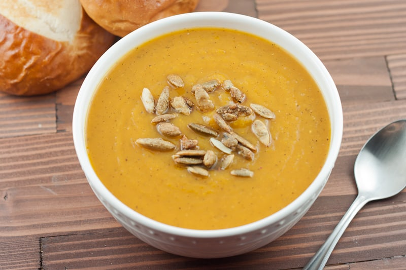 Bowl full of soup topped with roasted pumpkin seeds next to pretzel rolls and spoon