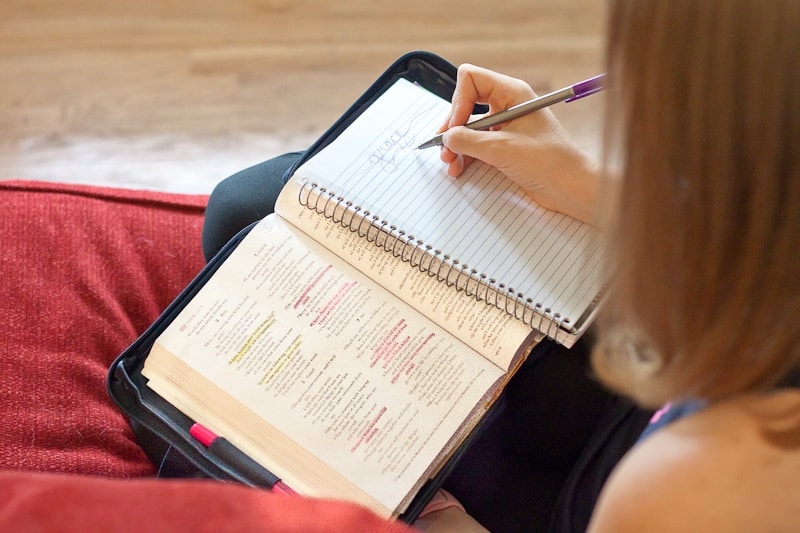 girl sitting on the couch with her Bible on her lap writing in a journal