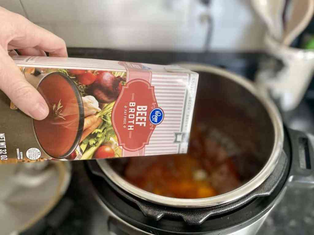 Pouring in a box of beef broth to the pot