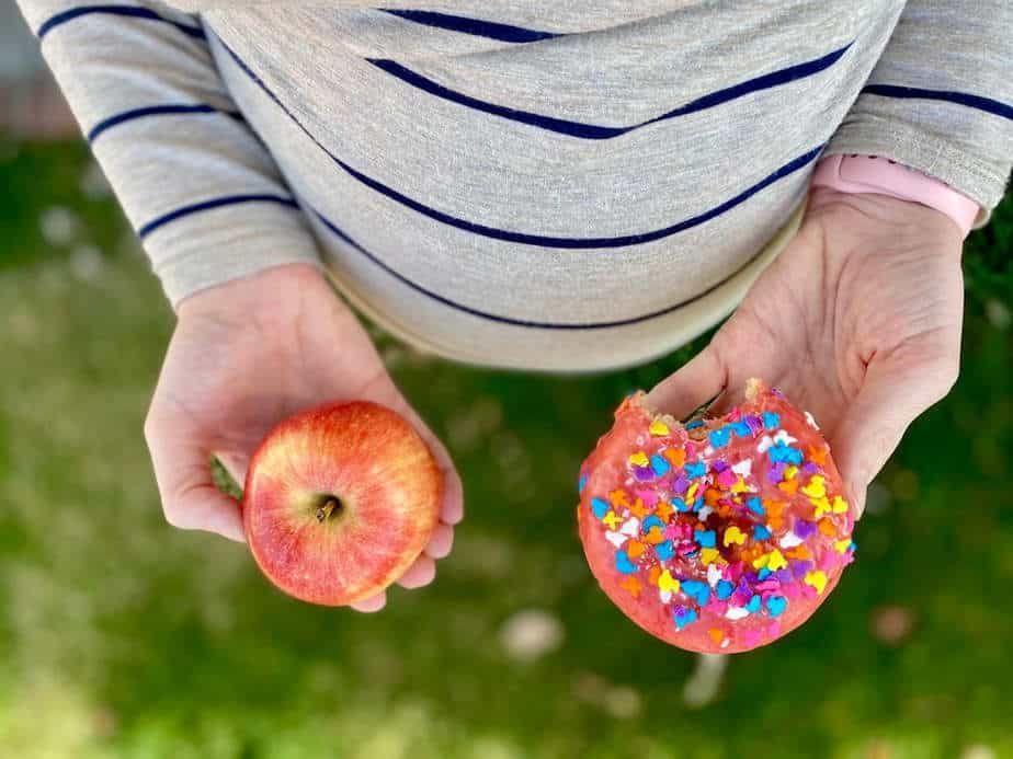 Pregnancy cravings - pregnant belly with one hand holding an apple and the other a donut