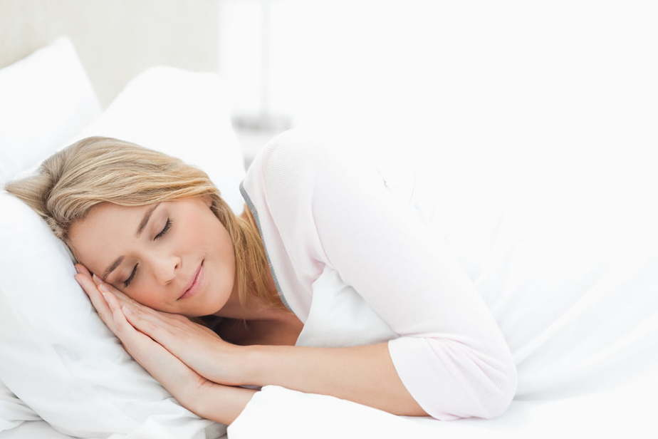 Bible verses on sleep and rest - woman restfully sleeping in a bed with comfy pillows and white sheets