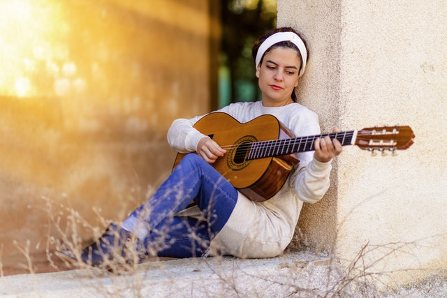 Woman playing the guitar fully focused