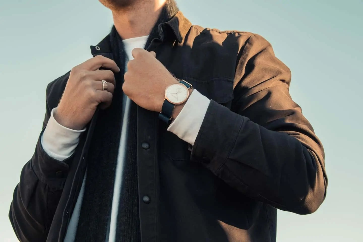 man adjusting his collar with chic watch on wrist