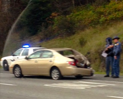 WSP trooper inspects collision damage to backend of car in 10/15/13 multi-vehicle accident