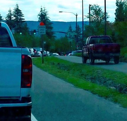 Driver attempting to avoid traffic backups by driving on Snoqualmie Pkwy walking path near Jacobia Street, 7/15/16