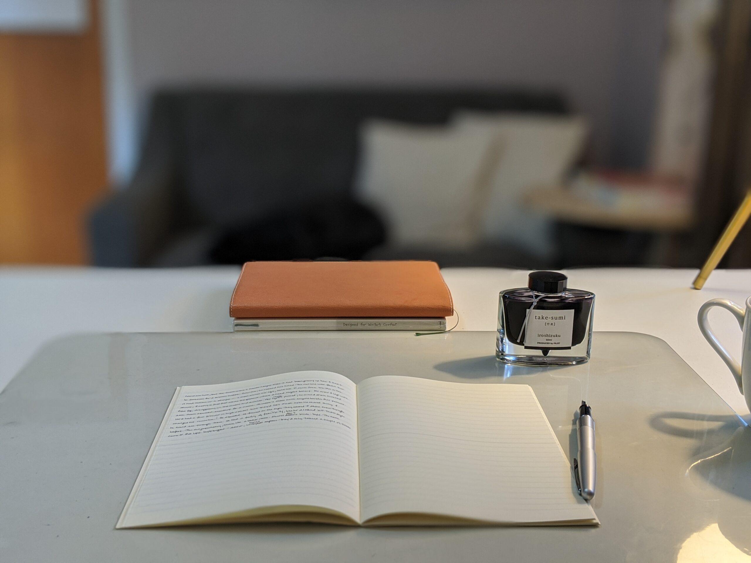 Open notebook a desk with fountain pen