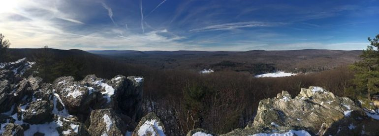 Panoramic view from rocky outcrop of snow covered campgrounds and mountains in the distance.