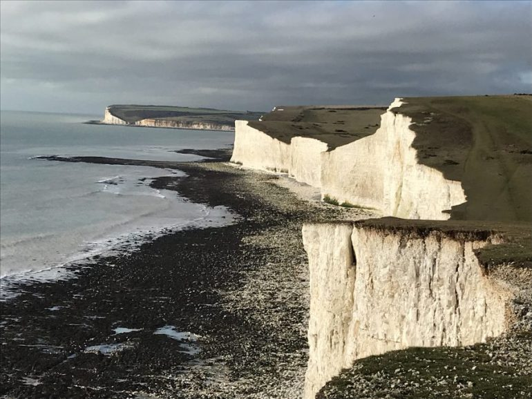 The sea meets the sheer white cliff faces at a beach covered in dark stones and seaweed.