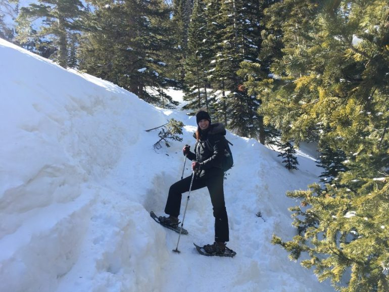 A smiling woman in snow shoes and holding trekking poles, walking on very thick snow.