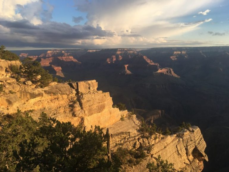As the sun rises, its light illuminates various sections of the canyon.