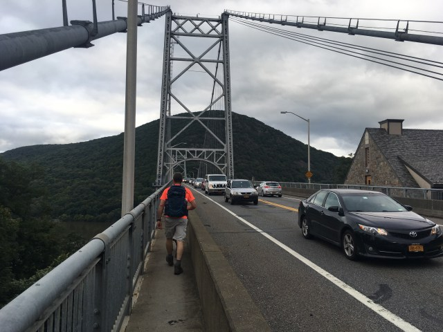 Walking along a car filled bridge, Anthony's Nose mountain peak ahead at the end of the walkway